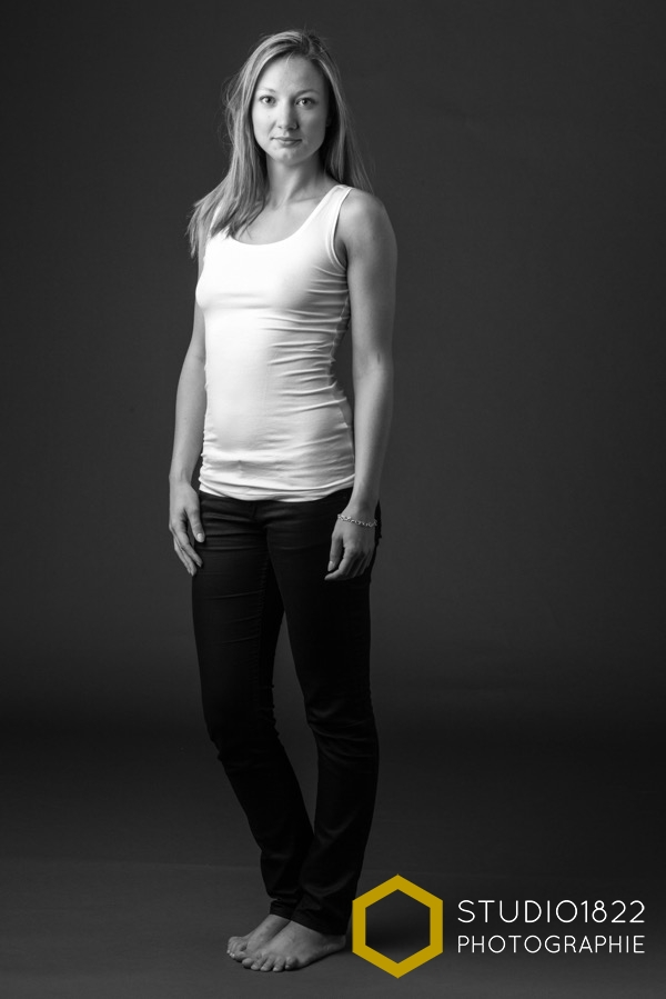 Portrait en pied en noir et blanc d'une jeune femme en débardeur blanc